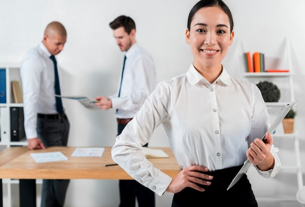 Confident smiling young businesswoman holding clipboard in hand with two businessman standing at backdrop
