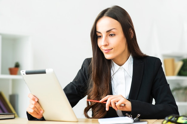 Confident smiling young businesswoman looking at digital tablet in the office