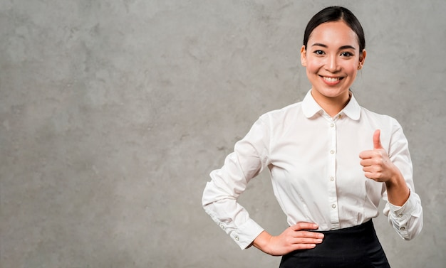 Confident smiling young businesswoman showing thumb up sign standing against grey wall