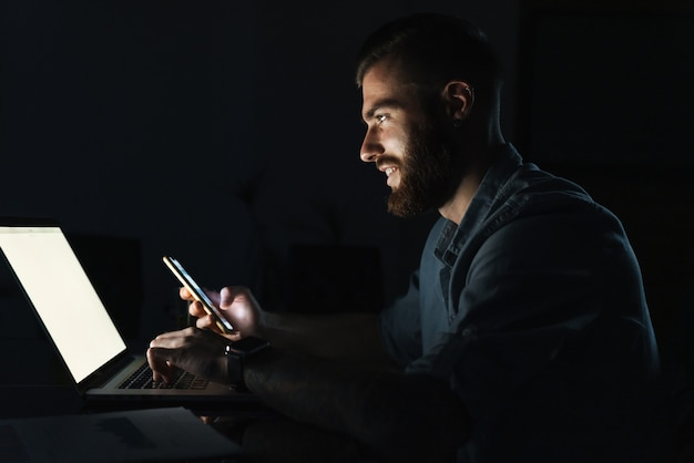 Уверенно улыбающийся молодой человек, работающий на портативном компьютере, сидя за столом в помещении ночью, используя мобильный телефон