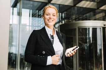 Confident smiling young woman holding mobile phone in hand