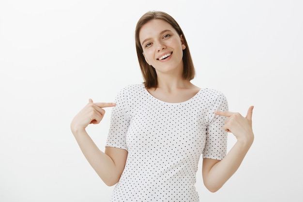 Confident smiling young woman student pointing at herself