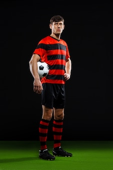 Confident soccer player with ball, play football