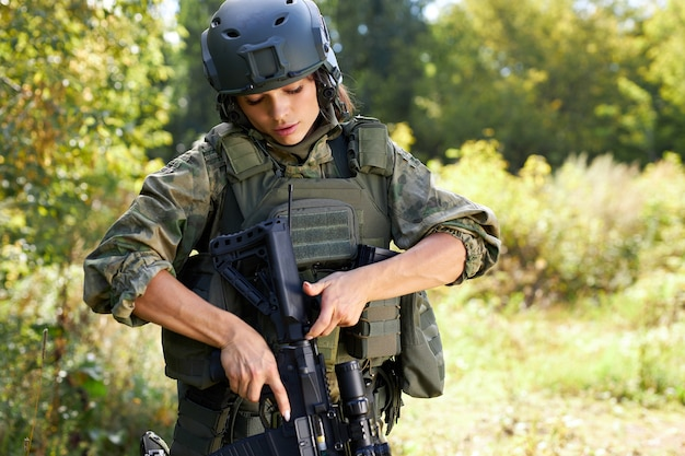 Confident soldier woman loading rifle in the forest