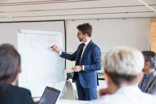 Confident speaker in eyeglasses talking near whiteboard