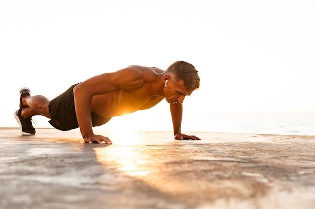 ビーチで腕立て伏せをしている自信のあるスポーツマン