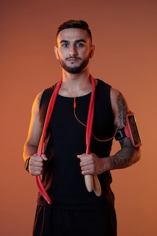 Confident sportsman with headphones and jumping rope
