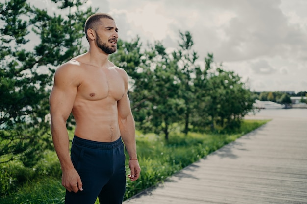 Confident sporty man bodybuilder has workout outdoor, looks thoughtfully into distance