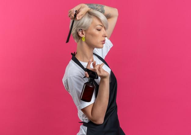 Fiducioso in piedi nella vista di profilo giovane bella barbiere femminile in uniforme che tiene strumenti da barbiere isolati su parete rosa pink