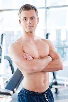自信のある強い男。腕を組んでジムに立っている間カメラを見て自信を持って若い筋肉の男