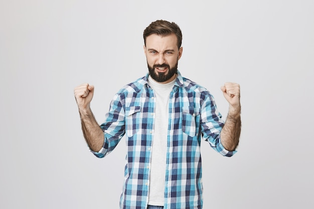 Confident strong middle-aged man clench fists determined win