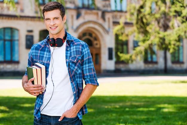 自信のある学生。本を持って大学の前に立って笑っているハンサムな若い男