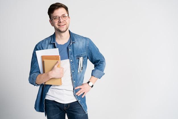 自信のある学生。本を持っているハンサムな若い男の肖像画。白で隔離。