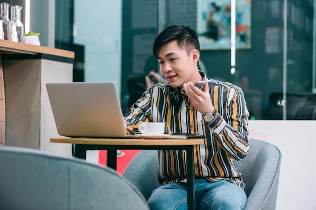 Уверенный студент сидит перед ноутбуком и смотрит на экран во время записи голосовых сообщений