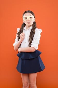 Уверенно учится студент. школьница в форме. ребенок в партийных очках. умный и умный ребенок на оранжевом фоне. обратно в школу. день знаний. счастливое детство. маленькая девочка студентка учеба.