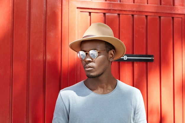Confident stylish african american guy wearing beige headdress and mirrored lens