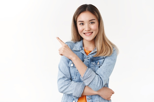 La ragazza bionda asiatica di bell'aspetto elegante e sicura consiglia di seguire la sua direzione puntando il dito indice nell'angolo in alto a sinistra sorridente fotocamera muro bianco sicuro di sé