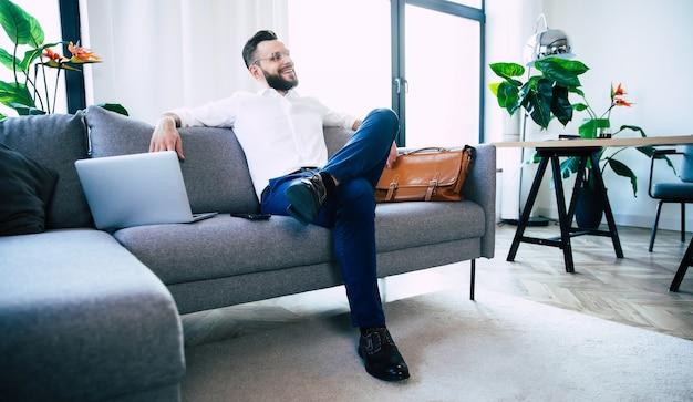 Уверенный в себе стильный красивый бородатый деловой человек в очках и формальной элегантной одежде сидит на диване в современном офисе или комнате