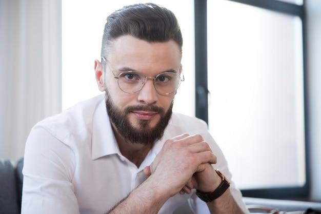 Уверенный в себе стильный красивый бородатый деловой мужчина в очках и формальной элегантной одежде, сидя на диване