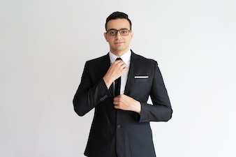 Confident stylish handsome young businessman adjusting necktie and looking at camera.