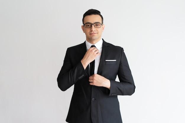 自信を持ってスタイリッシュなハンサムな若いビジネスマンは、ネクタイを調整し、カメラを見て。