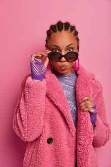 자신감 넘치는 스타일리쉬 한 여성은 입술을 둥글게 유지하고, 연인과 시시덕 거리며, 선글라스와 지난 패션 트렌드의 따뜻한 코트를 입고, 눈을 크게 뜨고, 분홍색 벽에 포즈를 취합니다. 매력과 스타일