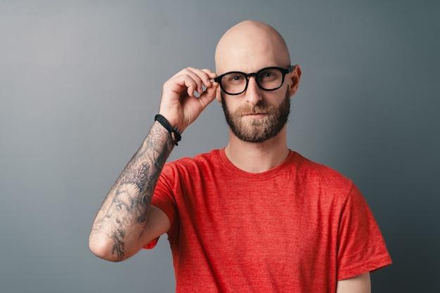 회색에 스튜디오에서 포즈, 문신 된 손으로 그의 검은 액자 안경을 고정 자신감 세련 된 젊은 수염 된 남자.