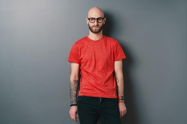 자신감이 세련 된 젊은 수염 된 남자 블랙 프레임 안경을 쓰고 스튜디오 o 회색에서 포즈.