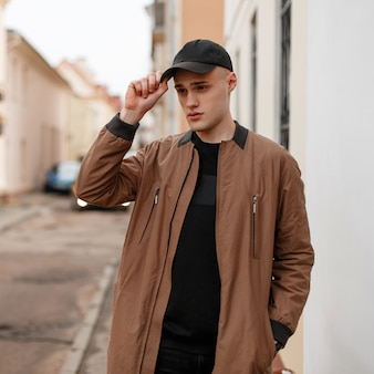 Confident stylish young man in a spring stylish long jacket in a black fashionable cap in a black t-shirt in jeans posing on the street near a vintage white building