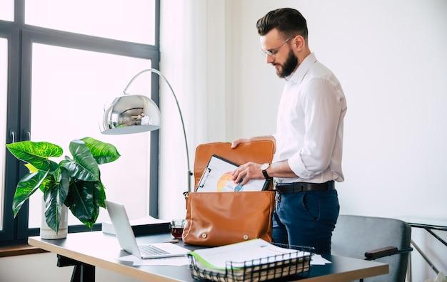 眼鏡をかけた自信を持って成功したひげを生やしたビジネスマンは、仕事の後に職場で彼のオフィスバッグにいくつかの文書を詰めています