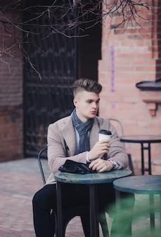 市で一杯のコーヒーを楽しんでいるコートで自信を持って成功した実業家