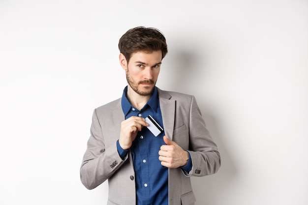 Confident and successful businessman looking self-assured while put plastic credit card in suit pocket, standing on white background.