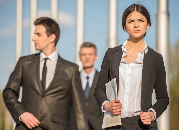 Confident successful businesspeople in suits at a meeting.