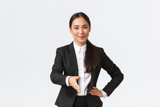 Уверенная успешная бизнес-леди в черном костюме протягивает руку для рукопожатия, приветствуя делового партнера с довольной решительной улыбкой, готовый подписать контракт, белая стена.