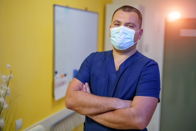 병원에서 자신감이 성공적인 의사. 마스크에 남성입니다. 의료 사무실에서 사진입니다.