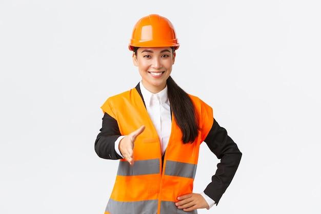 自信を持って成功した女性建築家、安全ヘルメット、反射ジャケット、握手のための手を伸ばす、建築エリアでビジネスパートナーに挨拶、白い背景に立って建設のリーダー