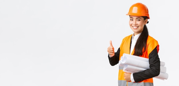 安全ヘルメットとジャケットのショーで自信を持って成功した女性のアジアの建設マネージャーの建築家...