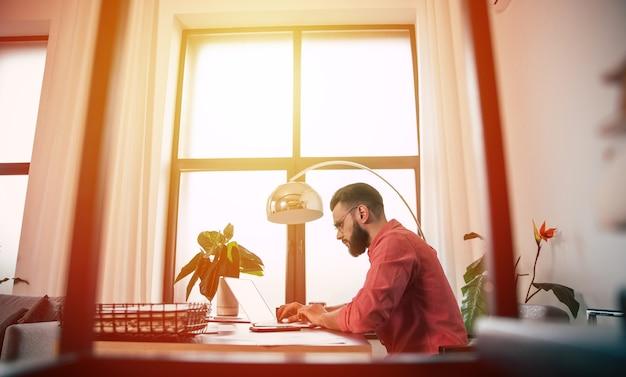 Уверенный успешный красивый бородатый мужчина в очках и элегантной повседневной одежде работает над ноутбуком