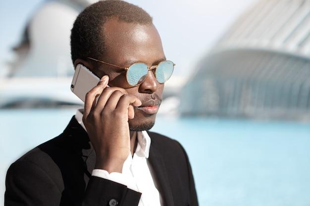 Уверенный успешный молодой предприниматель, имеющий деловой разговор по мобильному телефону