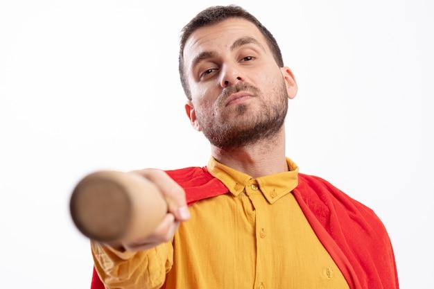 L'uomo sicuro del supereroe con il mantello rosso tiene fuori la mazza da baseball isolata sulla parete bianca
