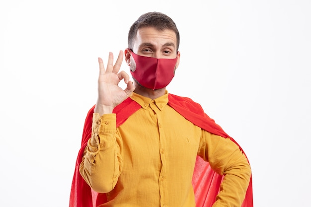 Confident superhero man with red cloak wearing red mask gestures ok hand sign isolated on white wall