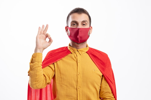 Confident superhero man with red cloak wearing red mask gestures ok hand sign looking at front isolated on white wall