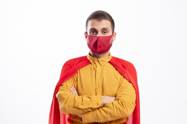 Confident superhero man with red cloak wearing red mask stands with crossed arms isolated on white wall