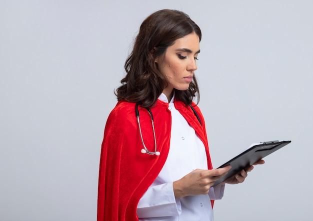 La superdonna sicura in uniforme del medico con il mantello rosso e lo stetoscopio tiene ed esamina la lavagna per appunti isolata sulla parete bianca
