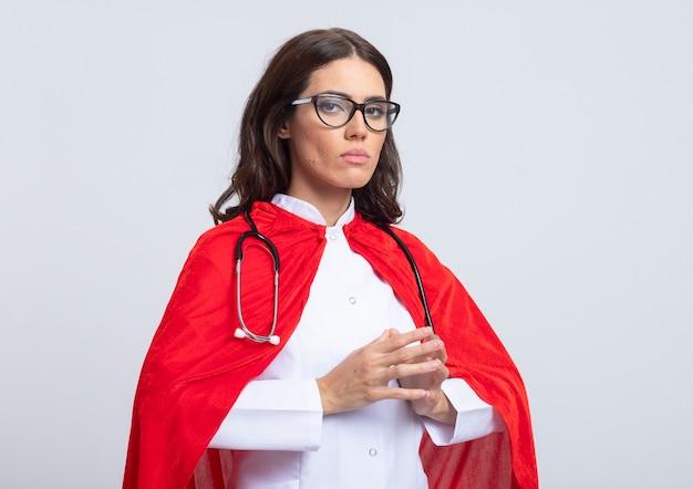 La superdonna sicura in uniforme del medico con il mantello rosso e lo stetoscopio in vetri ottici tiene le mani insieme isolate sulla parete bianca