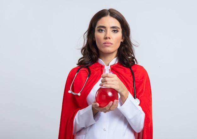 흰색 벽에 고립 된 유리 플라스크에 빨간 화학 액체를 들고 빨간 케이프와 청진기와 의사 유니폼 자신감 슈퍼 우먼