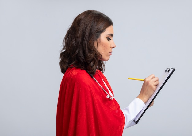 Уверенная суперженщина в медицинской форме с красной накидкой и стетоскопом стоит боком, держа в руках буфер обмена и карандаш, изолированные на белой стене