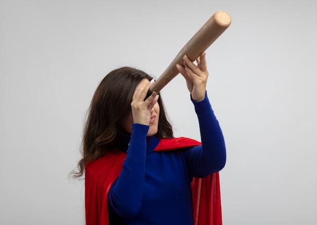 빨간 망토와 자신감이 슈퍼 우먼은 흰 벽에 고립 된 그녀의 눈 앞에서 야구 방망이를 보유하고 있습니다.