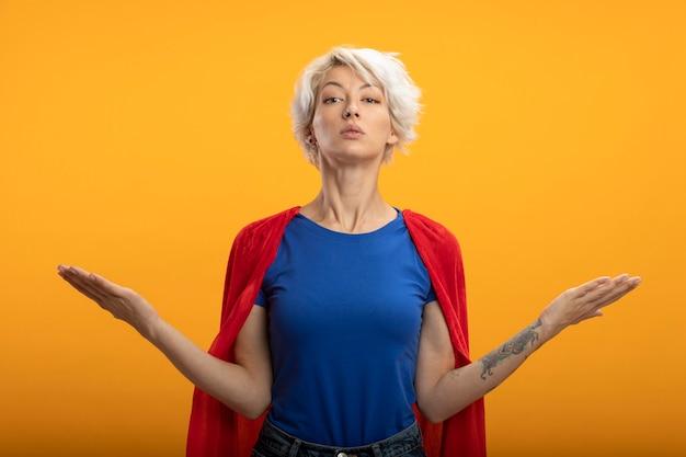 赤いマントを持つ自信のあるスーパーウーマンは、オレンジ色の壁に隔離された手を開いて保持します