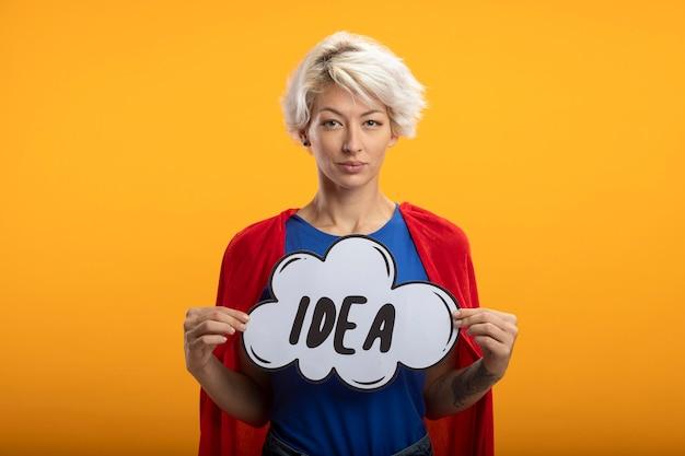 赤いマントと自信を持ってスーパーウーマンはオレンジ色の壁に分離されたアイデアの泡を保持します